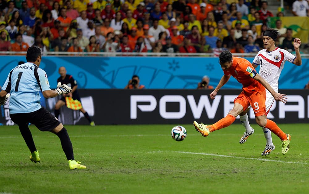 Netherlands' Robin van Persie takes a shot on Costa Rica's goalkeeper Keylor Navas while being defended by Christian Bolanos during the World Cup quarterfinal soccer match at the Arena Fonte Nova in Salvador, Brazil.