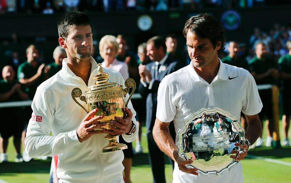 Serbia's Novak Djokovic, left, holds his trophy after defeating Switzerland's Roger Federer, right, in the men's singles final match at the All England Lawn Tennis Championships in Wimbledon.