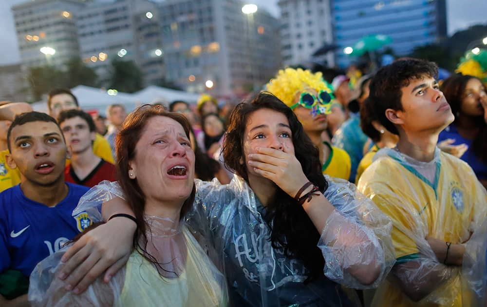 Brazil soccer fans cry as they watch their team lose 7-1 to Germany at a World Cup semifinal match on a live telecast inside the FIFA Fan Fest area on Copacabana beach in Rio de Janeiro, Brazil.