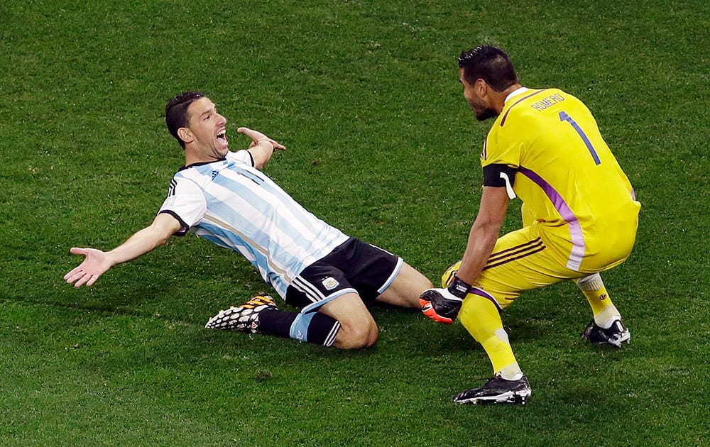 Argentina's Maxi Rodriguez celebrates with Argentina's goalkeeper Sergio Romero after scoring the last penalty during the World Cup semifinal soccer match between the Netherlands and Argentina at the Itaquerao Stadium in Sao Paulo Brazil.