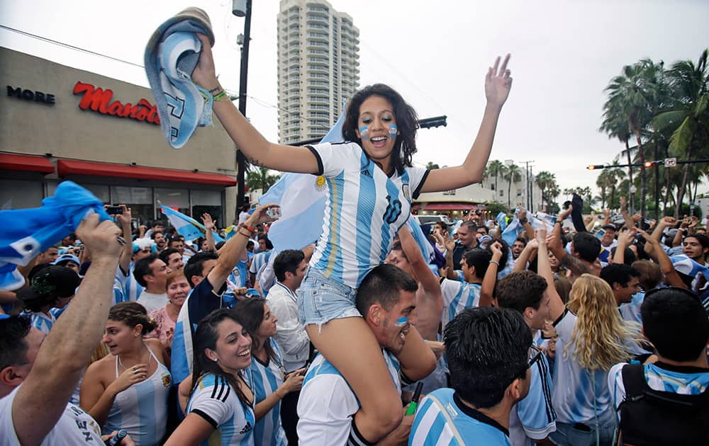 Soccer fans celebrate outside Manolo Restaurant in Miami Beach, Fla., after Argentina defeated the Netherlands 4-2 in a penalty shootout after a 0-0 tie after extra time to advance to the finals.
