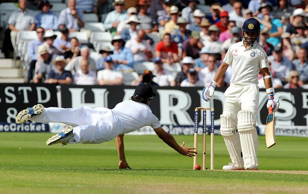 England's Alastair Cook dives but fails to catch India's Ajinkya Rahane, right. A few balls later Alastair Cook caught Ajinkya Rahane bowled by England's Liam Plunkett for 32 runs during day one of the first Test between England and India at Trent Bridge cricket ground, Nottingham.