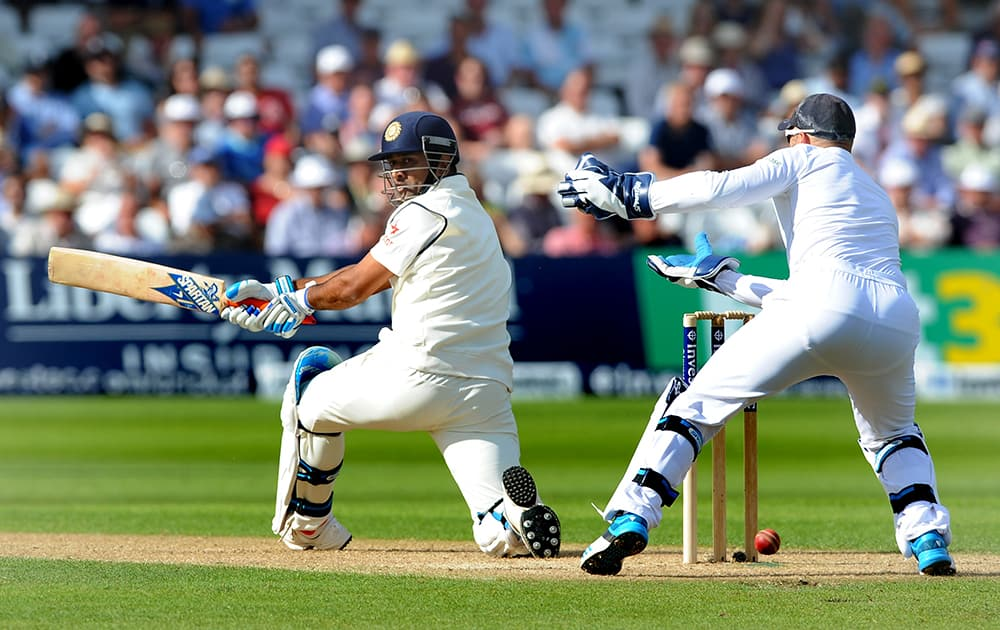 India's M.S. Dhoni, left, plays a shot past England wicket keeper Matt Prior during day one of the first Test between England and India at Trent Bridge cricket ground, Nottingham