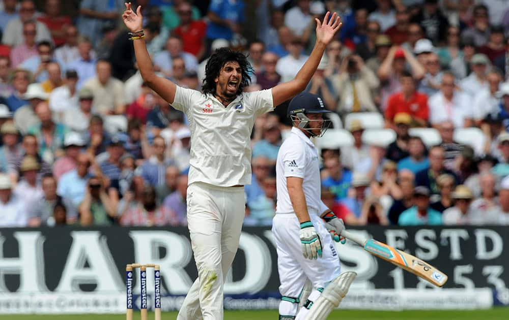 Ishant Sharma celebrates after bowling England's Ian Bell, right, caught M S Dhoni for 25 runs during day three of the first Test between England and India at Trent Bridge cricket ground, Nottingham, England.