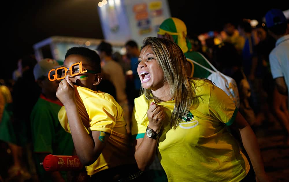 Fans of the Brazil national soccer team cheer for their team in front a video camera after a live broadcast of the World Cup third-place soccer match between Brazil and the Netherlands, inside the FIFA Fan Fest area on Copacabana beach, Rio de Janeiro, Brazil.