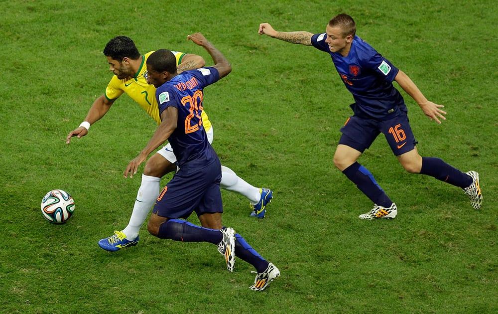 Brazil's Hulk dribbles past Netherlands' Georginio Wijnaldum during the World Cup third-place soccer match between Brazil and the Netherlands at the Estadio Nacional in Brasilia, Brazil.