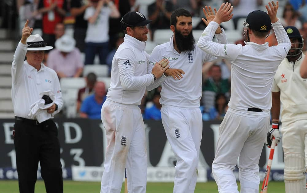 England's Moeen Ali, 2nd left, celebrates with Ian Bell and Gary Ballance, right, after bowling India's Murali Vijay caught Matt Prior for 52 runs during day four of the first Test between England and India at Trent Bridge cricket ground, Nottingham, England.