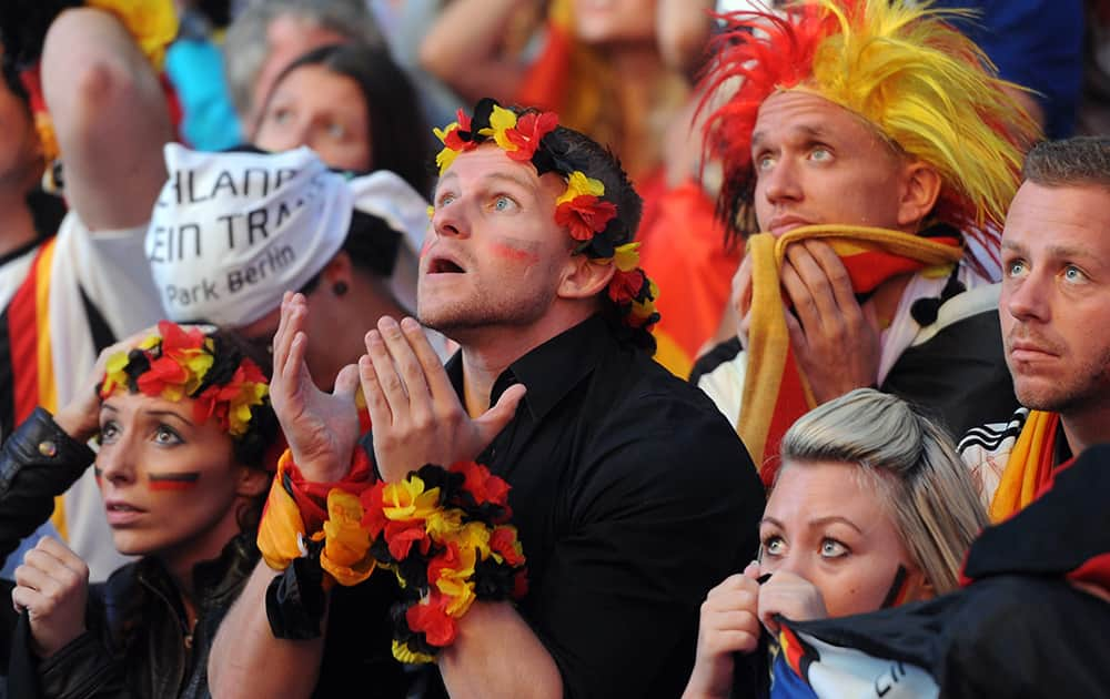 German soccer fans react as they watch a live broadcast of the final match between Germany and Argentina at the soccer World Cup 2014 in Rio de Janeiro, Brazil.