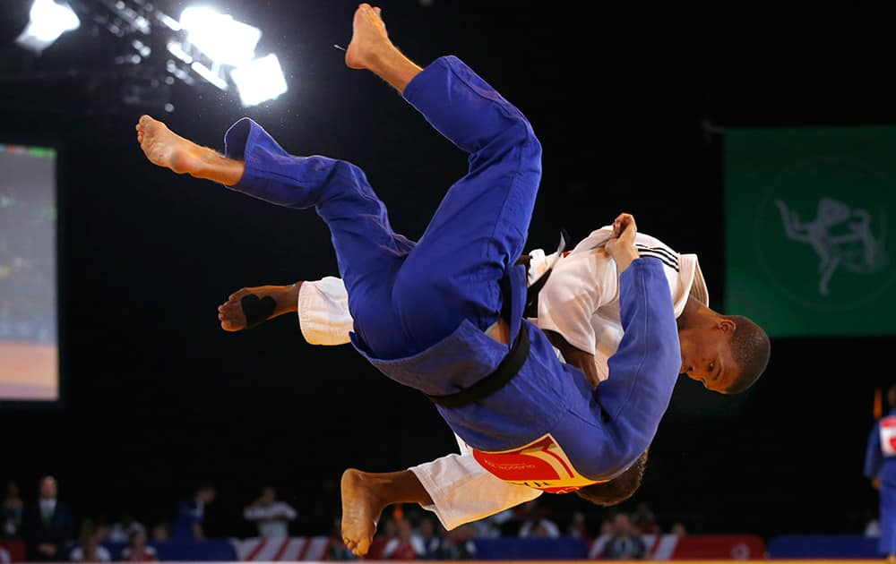 Siyabulela Mabulu of South Africa, in white, throws Jamie Macdonald of Wales during their men's 66kg judo preliminary round bout at the Commonwealth Games Glasgow 2014, in Glasgow, Scotland.