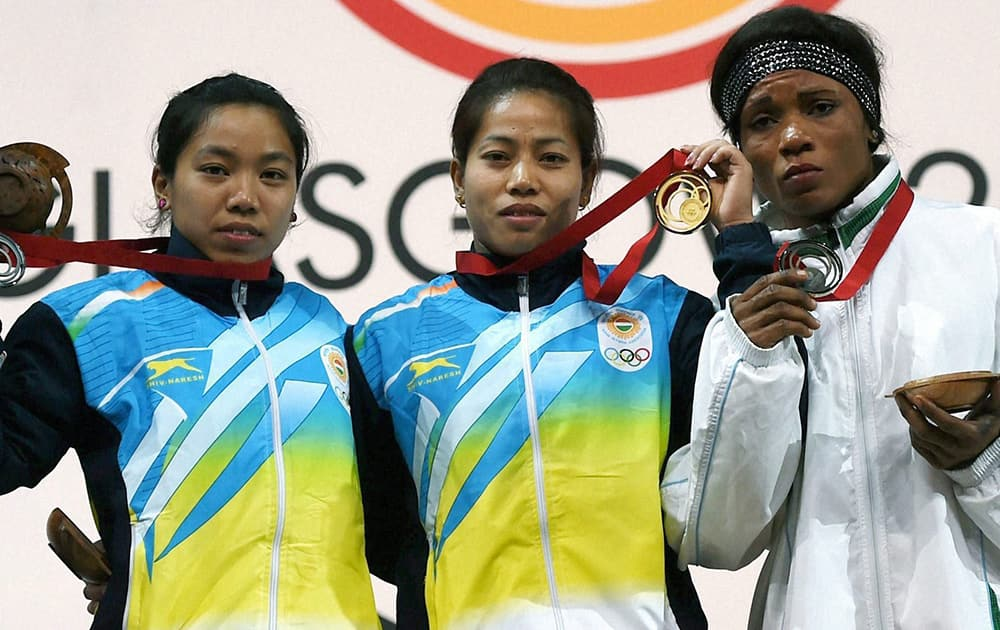 India's gold medalist Sanjita Khumukcham and compatriot silver medallist Chanu Saikhom with bronze medalist Nigeria Opara Nkechi during the medal presentation ceremony of 48-kg women's weightlifting event at the Commonwealth Games in Glasgow, Scotland.