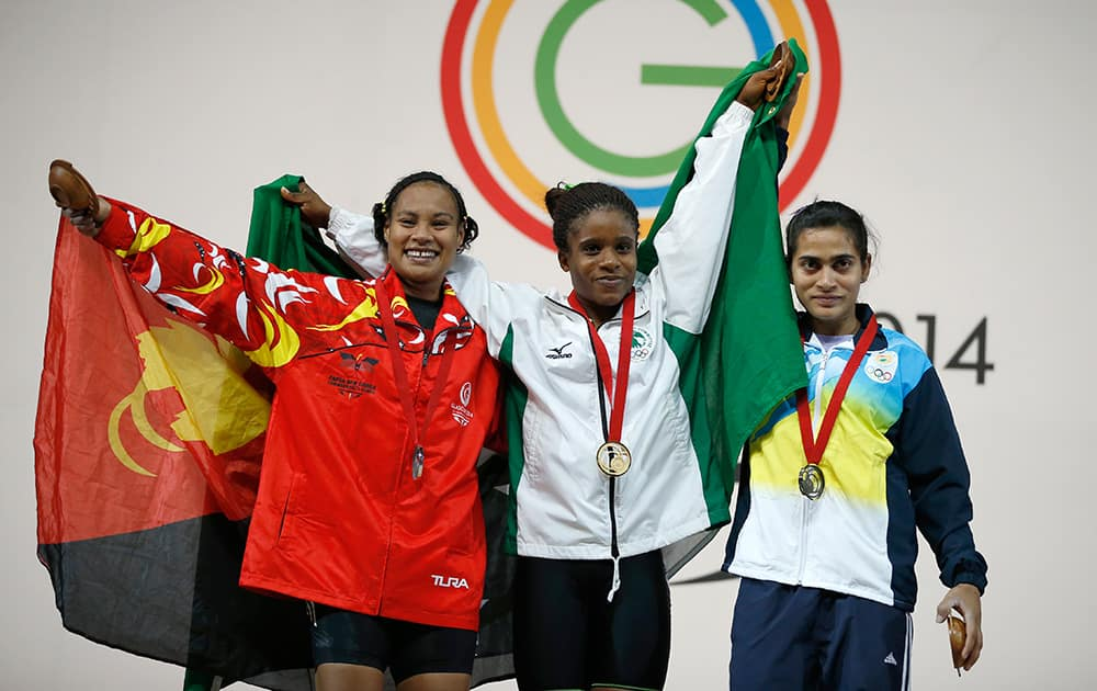 Chika Amalaha of Nigeria, centre , gold medal, Dika Toua of Papua New Guinea, left silver medal and Santoshi Matsa of India bronze medal pose for photographs with their medals for the women's weightlifting 53 kg after the medal ceremony at the Commonwealth Games Glasgow 2014, in Glasgow, Scotland.