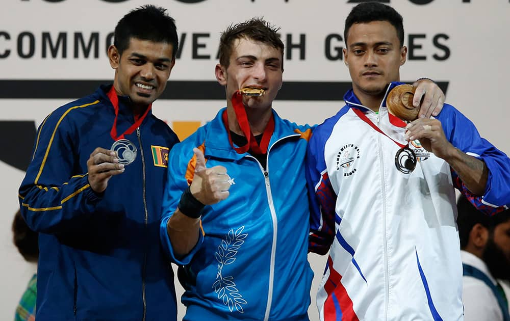 Gold medalist Dimitris Minasidis, of Cyprus, centre, Sudesh Peiris of Sri Lanka, left, silver medal and Vaipava Ioane of Samoa bronze medal pose for photographs after the medal ceremony for the men's 62 weightlifting contestat the Commonwealth Games Glasgow 2014, in Glasgow, Scotland.