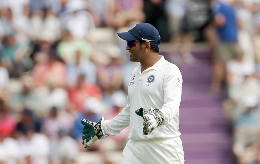 India's captain and wicketkeeper Mahendra Singh Dhoni gives a teammate fielding instructions during the first day of the third cricket test match of the series between England and India at The Ageas Bowl in Southampton, England.