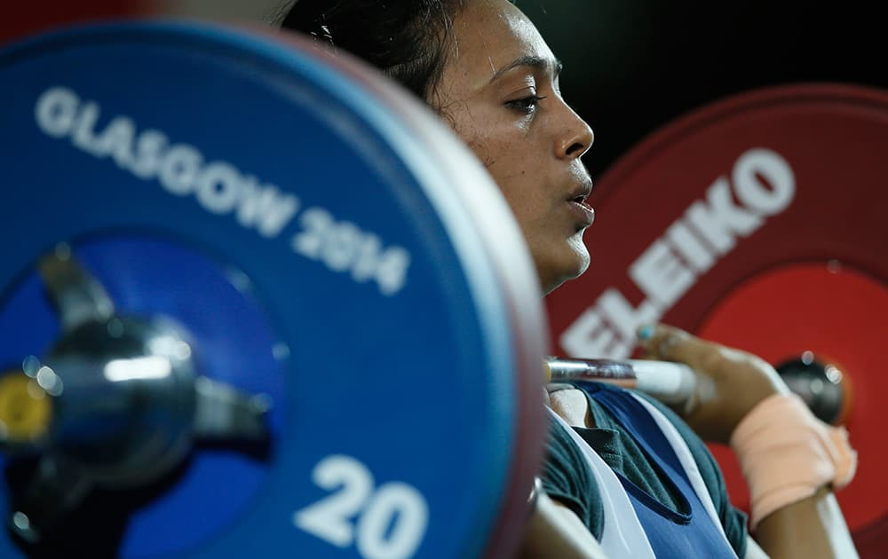 Punam Yadav of India holds the wight as she lifts during the women's 63 kg weightlifting competition at the Commonwealth Games Glasgow 2014, in Glasgow, Scotland.