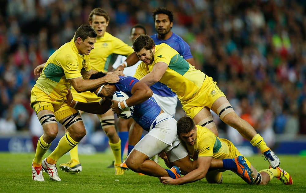 Ed Jenkins, left, of Australia with teammates Liam Gill, second right, and Sean McMahon, on floor, tackle Levi Asifaanatala of Samoa during their rugby sevens bronze medal match at the Commonwealth Games Glasgow 2014, in Glasgow, Scotland.