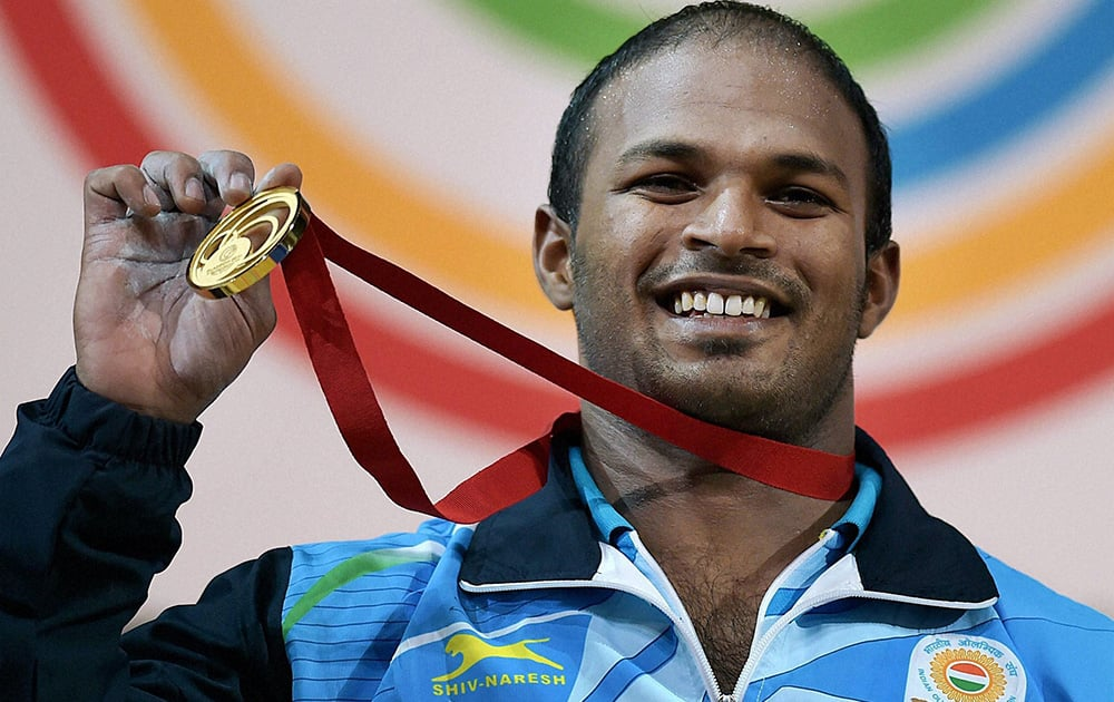 Sathish Sivalingam of India shows the medal after winning the gold in the Men's Weightlifting 77kg category during the Glasgow 2014 Commonwealth Games at Scottish Exhibition And Conference Centre in Glasgow,Scotland.