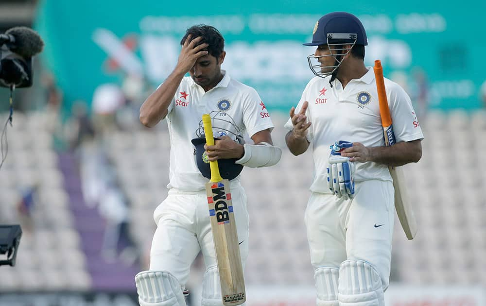 Mahendra Singh Dhoni, right, and Mohammed Shami walk off the field of play at the end of play on the third day of the third cricket test match of the series between England and India at The Ageas Bowl in Southampton.
