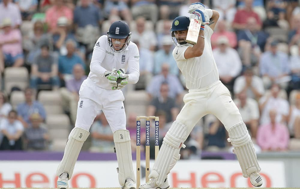 Virat Kohli hits a shot watched by test debutant England wicketkeeper Jos Buttler during the fourth day of the third cricket test match of the series between England and India at The Ageas Bowl in Southampton