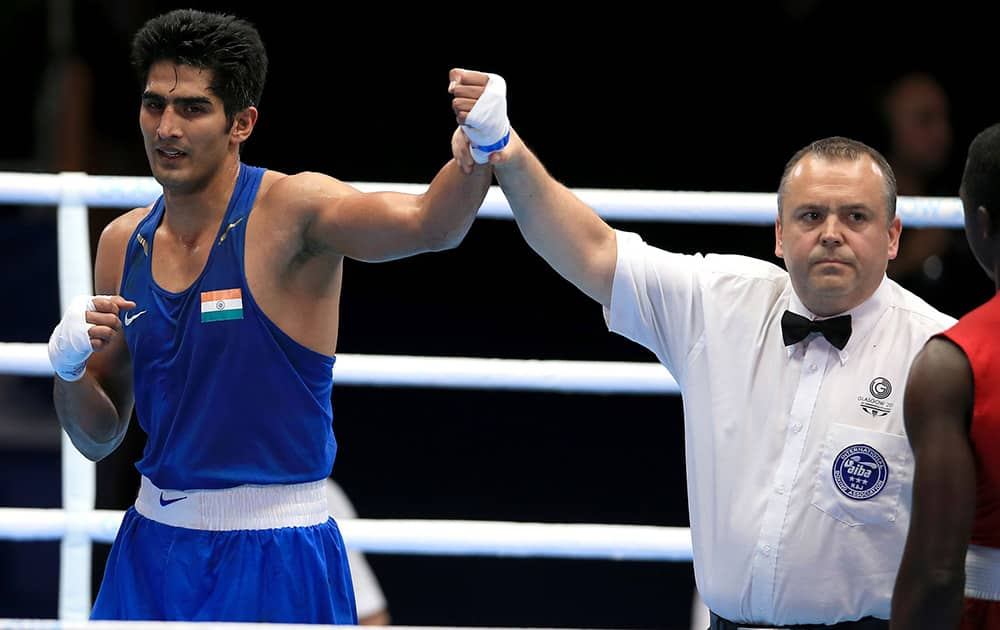 Vijender celebrates victory against Trinidad and Tobago's Aaron Prince after their Men's middle weight quarterfinal during the 2014 Commonwealth Games in Glasgow, Scotland.