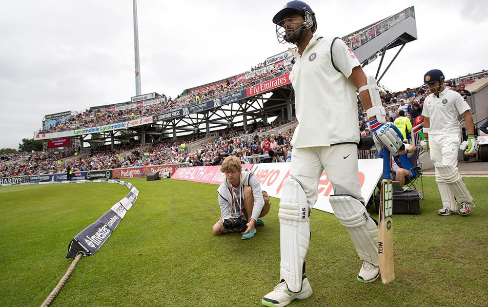India's Murali Vijay and Gautam Gambhir take to the pitch as play begins at Old Trafford cricket ground on the first day of the fourth test match of their five match series against England, in Manchester, England.