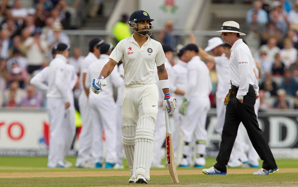 India's Virat Kohli walks from the pitch after losing his wicket for 0 off the bowling of England's James Anderson at Old Trafford cricket ground on the first day of the fourth test match of their five match series, in Manchester, England.