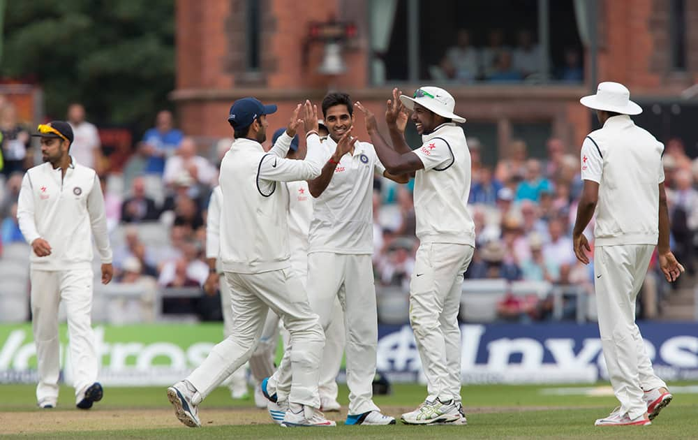 Bhuvneshwar Kumar, centre, celebrates with teammates after taking the wicket of England's Chris Jordan for 13 at Old Trafford cricket ground on the second day of the fourth test match of their five match series, in Manchester, England.