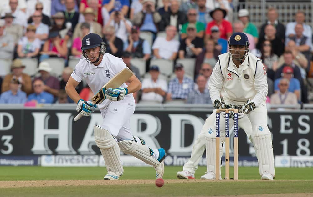 England's Jos Buttler takes a run as India's captain MS Dhoni looks on, on the second day of the fourth test match of their five match series at Old Trafford cricket ground, in Manchester, England.
