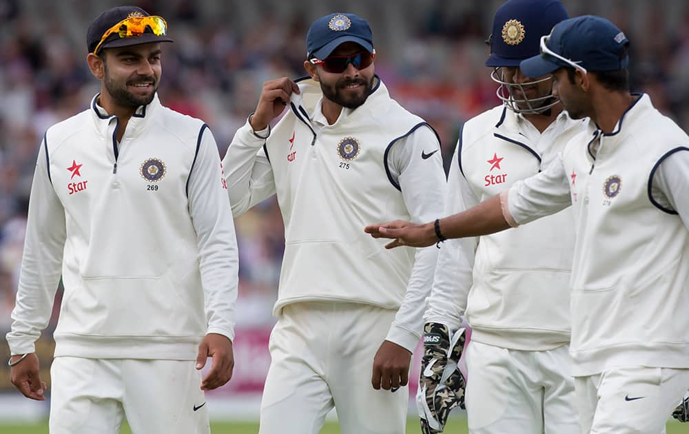 India's Ravindra Jadeja smiles he walks from the pitch with teammates after taking the wicket of James Anderson for 9, as England post a total of 367 on the third day of the fourth test match of their five match series at Old Trafford cricket ground, in Manchester, England.
