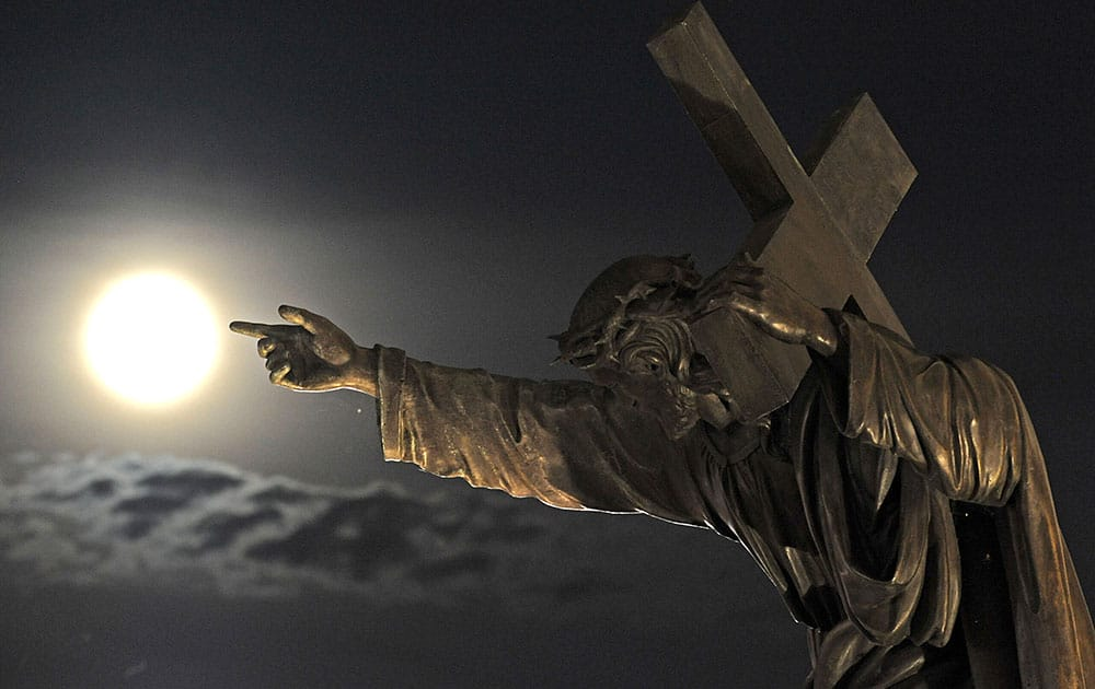 A SUPERMOON RISES ABOVE A JESUS CHRIST STATUE IN FRONT OF THE HOLY CROSS CHURCH IN WARSAW, POLAND.
