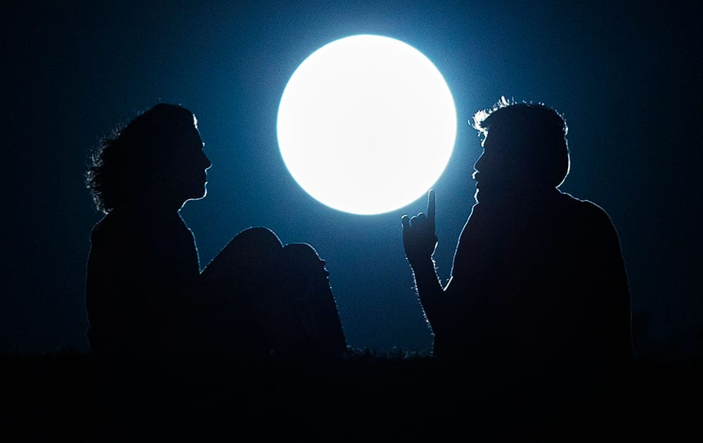 A couple talk as they sit against the perigee moon, also known as a supermoon, in Madrid.