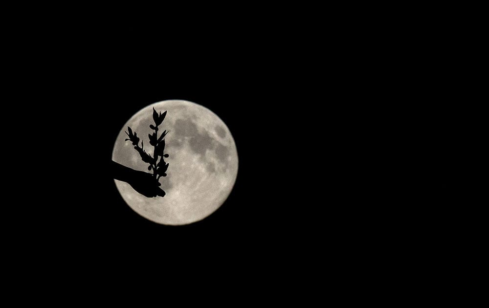A supermoon appears behind the Angel of Peace sculpture, in London.