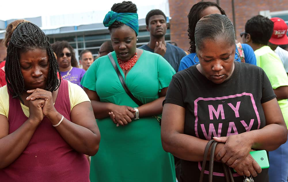 A prayer vigil was held in front of the Ferguson, Mo. police department on Sunday, Aug. 10, 2014, one day after a Ferguson officer shot and killed Michael Brown. From left are Martha Hightower, Leah Clyburn and Marie Wilson. `I`m just tired of (the police) getting away with killing our youths,` said Hightower.