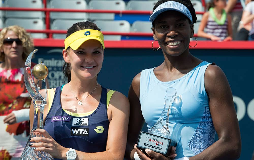 Agnieszka Radwanska, left, of Poland poses with Venus Williams of the United States after winning the final at the Rogers Cup tennis tournament.