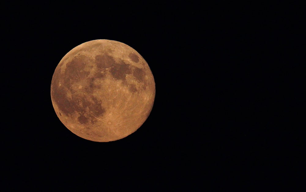The supermoon appears yellow as the sky darkens over Edgartown, Mass., on the island of Martha`s Vineyard. President Barack Obama and his family are vacationing on the island.