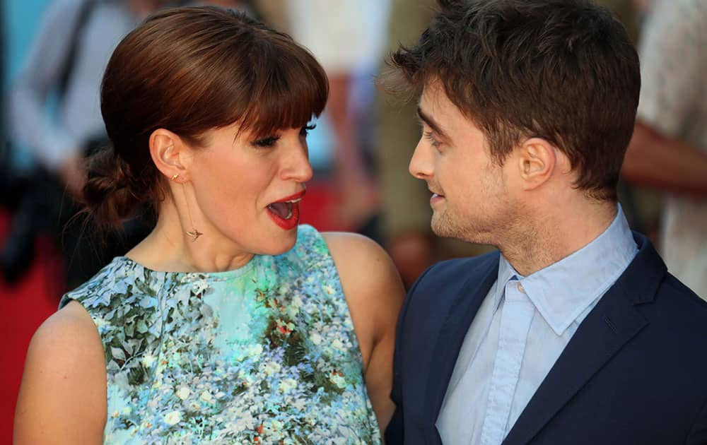 British actors Daniel Radcliffe and Jemima Rooper, react, as they arrive on the red carpet for the UK premiere of What If, at the Odeon West End in central London.