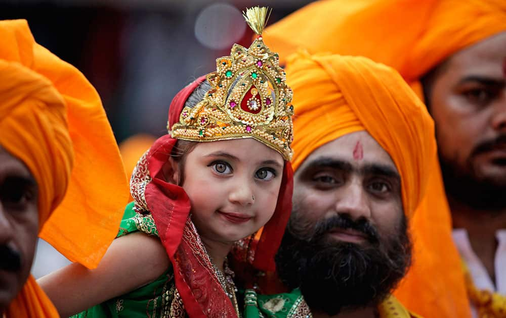 An Indian man carries a girl dressed as Radha, consort of Hindu god Krishna, during a procession on the eve of Janmashthami festival in Jammu.