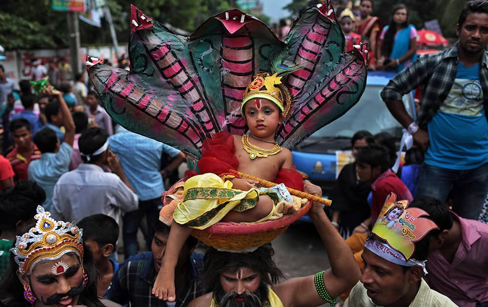 A Bangladeshi Hindu devotee carries on his head, a child dressed like Hindu god Krishna in a basket during a procession to celebrate 'Janmashtami' or Krishna's birth day in Dhaka, Bangladesh.