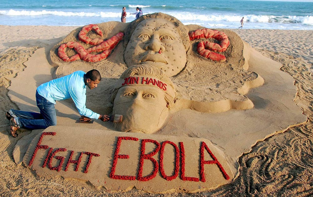 "Sand artist Sudarsan Pattnaik creates a sand sculpture on EBOLA virus with a message ""Join hands to fight EBOLA"" at Puri beach in Odisha."