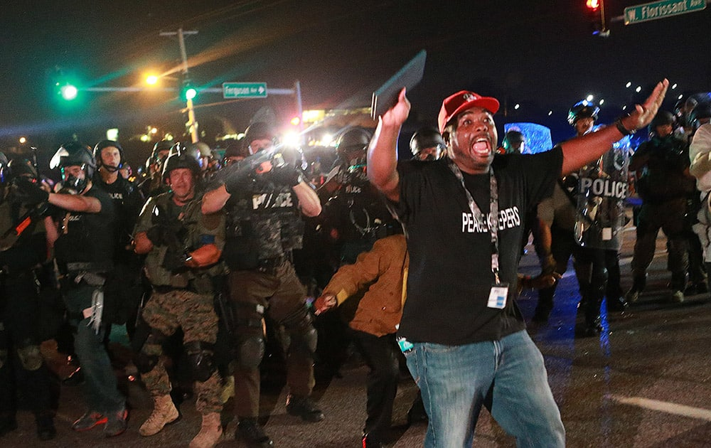 A citizen peacekeeper tries to keep protesters back as police advance, in Ferguson, Mo.