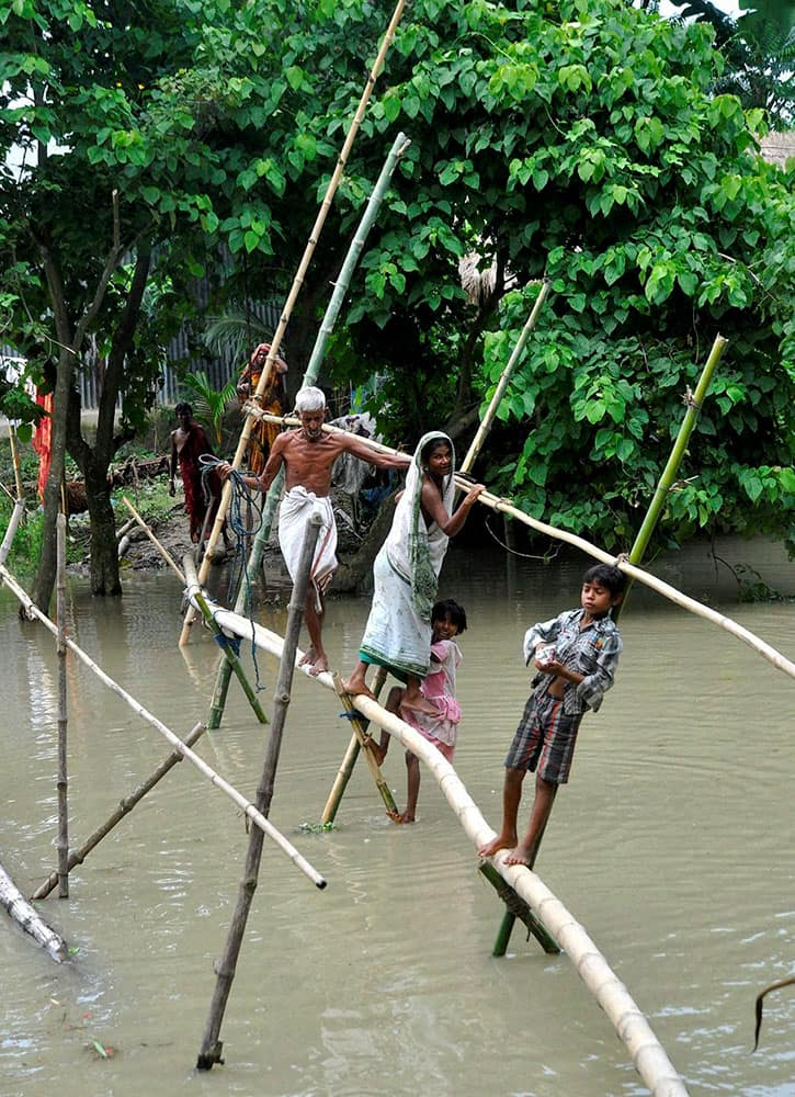 Indian villagers use a bamboo structure to move across a flooded village in Morigaon district of northeastern Assam state, India.