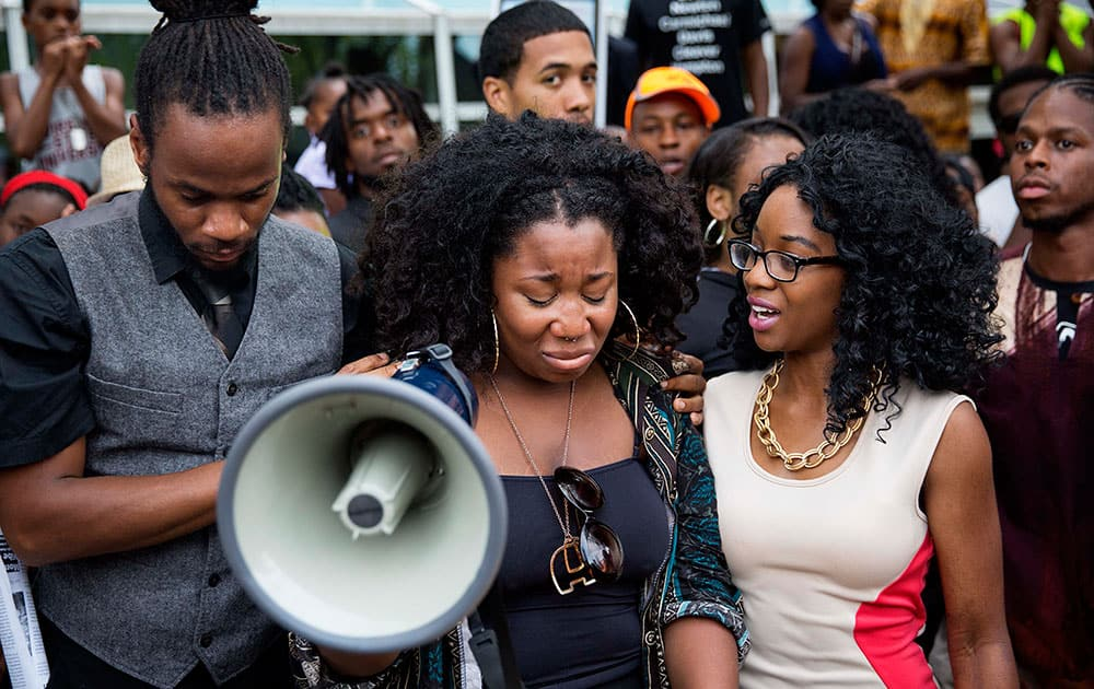 Elle Lucier, center, is comforted by Shawn Walton, left, and Sheola Farquharson as she pauses while fighting back tears during a speech at a rally in response to the fatal shooting of Michael Brown,  in Atlanta.