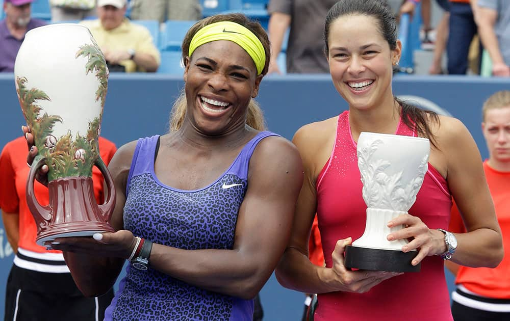 Serena Williams and Ana Ivanovic, from Serbia, pose with their trophies after Williams defeated Ivanovic 6-4, 6-1, in the women`s final match at the Western & Southern Open tennis tournament.