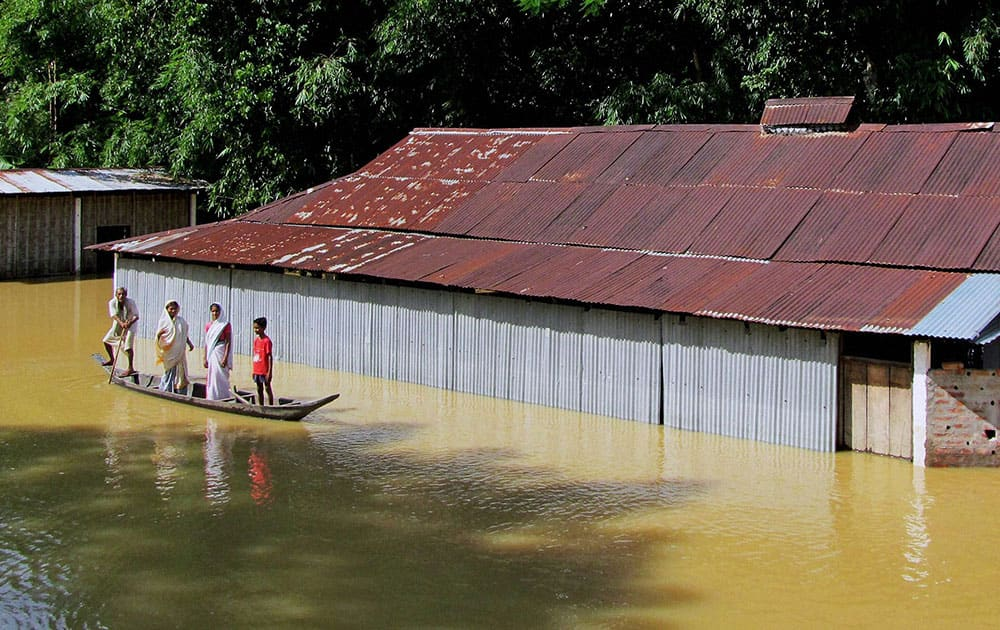 A family shifting to safer place by a boat in flood affected Teok, Jhanjimukho in Jorhat district of Assam.
