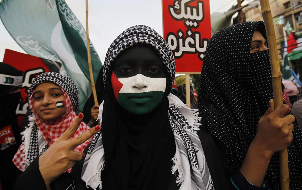 A supporter of Pakistani religious party Jamaat-e-Islami, with her face painted with a representation of the Palestinian flag, and others rally against the Israeli bombings in the Gaza, in Karachi.