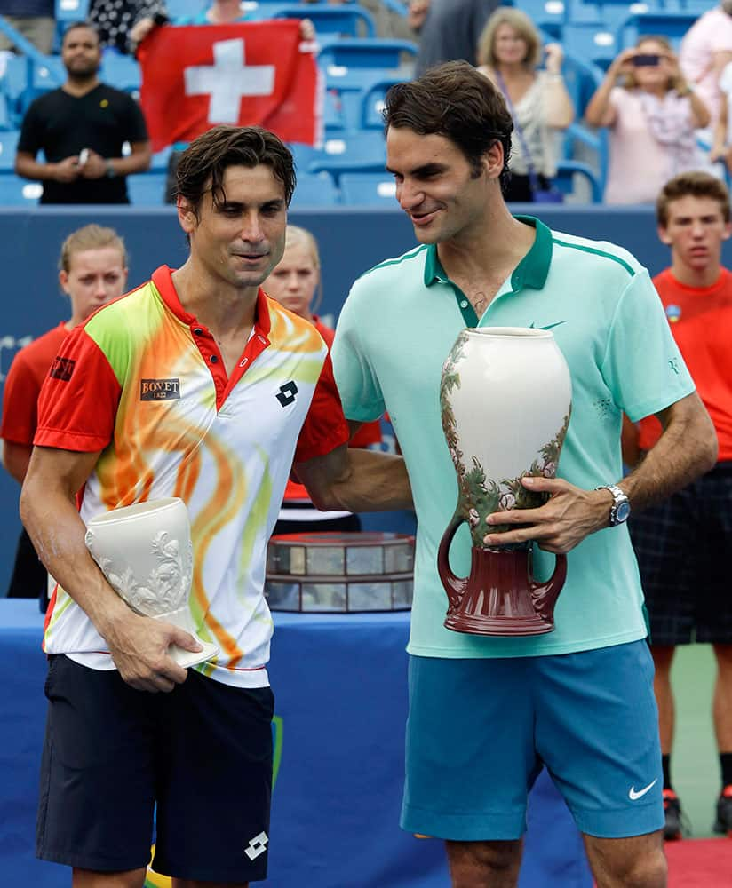 David Ferrer, from Spain, left, and Roger Federer, from Switzerland, congratulate each other as they pose with their trophies after Federer defeated Ferrer 6-3, 1-6, 6-2, to win the Western & Southern Open tennis tournament.