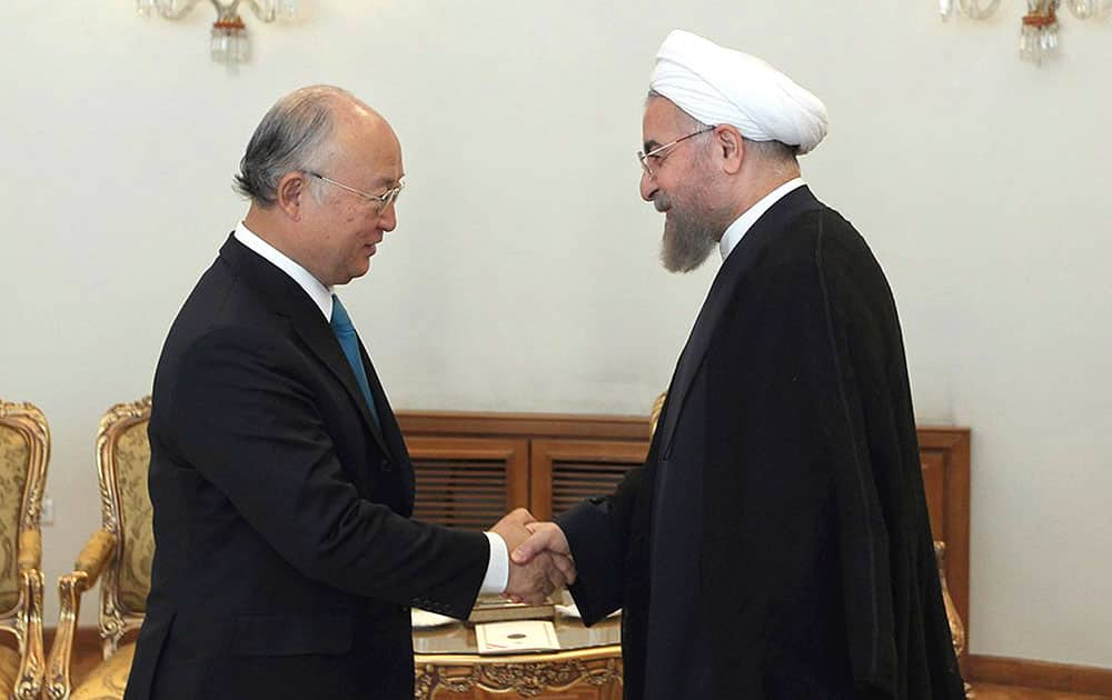 In this photo released by the official website of the office of the Iranian Presidency, Iran`s President Hassan Rouhani, right, shakes hands with Director General of the International Atomic Energy Agency Yukiya Amano at the start of their meeting in Tehran, Iran.