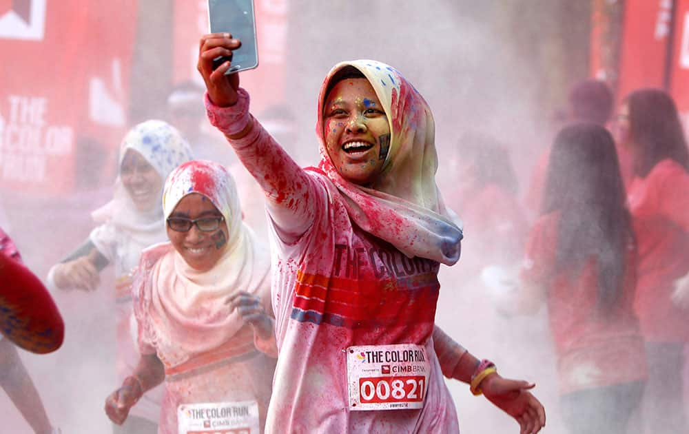 A participant takes a selfie as she runs through a `color station` during the five-kilometer color run event in Kuala Lumpur, Malaysia.