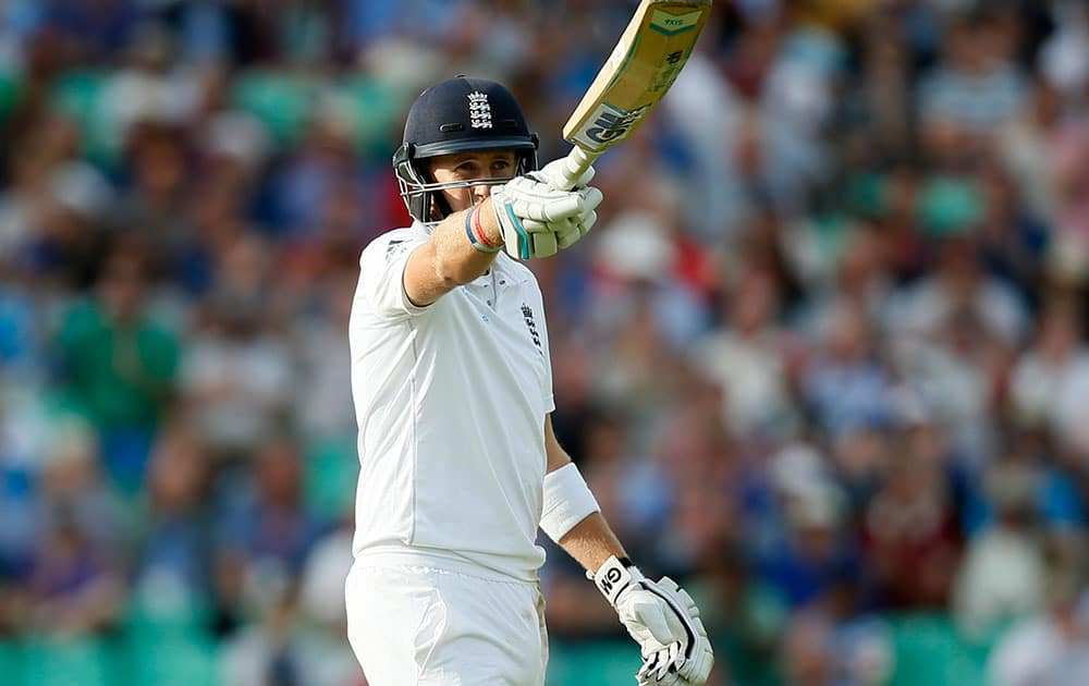 England`s Joe Root celebrates getting 50 runs not out during the second day of the fifth test cricket match against India at Oval cricket ground in London.