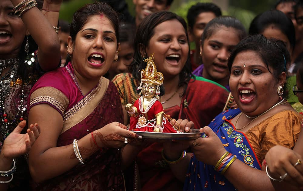 Indian teachers hold an idol of Hindu god Krishna and sings devotional songs during Janmashthami celebrations at a school in Ahmadabad, India.