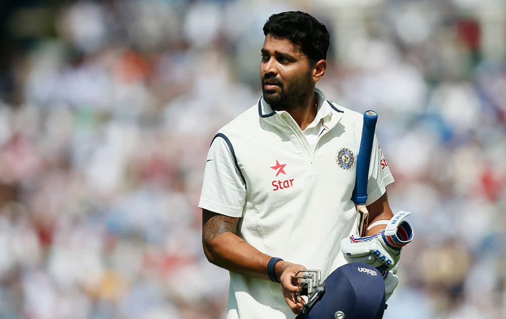 Murali Vijay looks at a large video screen to see how he lost his wicket, caught out by England's Joe Root off the bowling of Chris Woakes, during the first day of the fifth test cricket match at Oval cricket ground in London.